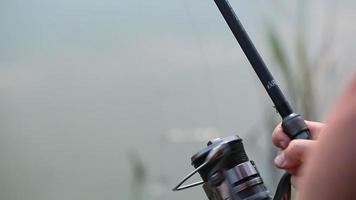 pesca nel fiume, pescatore con una canna da pesca sulla riva del fiume. uomo pescatore cattura un pesce con la bobina di filatura video
