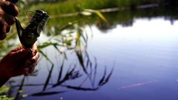 l'uomo gira una bobina su un cucchiaio di esca mentre pesca nel bellissimo lago in estate
