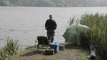 pensionista pescando nas margens de um lago inglês