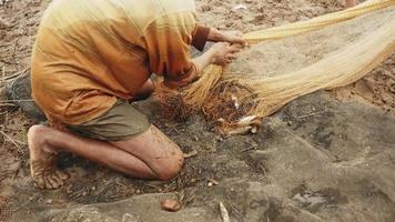 pescatore districare la rete da pesca e rimuovere i detriti legnosi