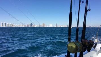 Spinnruten sind auf einem Boot. im Hintergrund die Stadt.