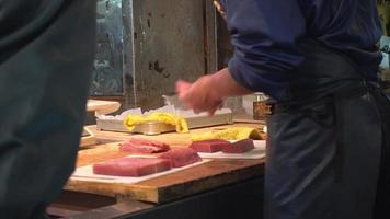 açougueiro de peixes corta carne de atum no mercado tsukiji de frutos do mar