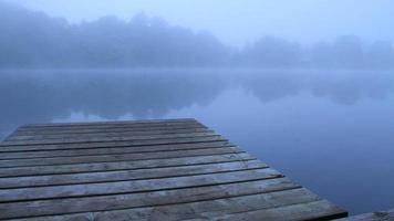 blaues Dock am nebligen Morgensee