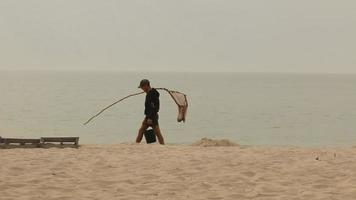 The fisherman passes along the beach