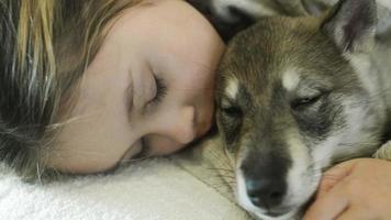 niña duerme abrazando mascota