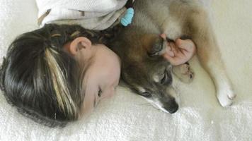 Mädchen schläft ein und umarmt einen schlafenden Welpen