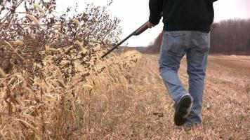 hombre caminando con pistola a través del campo