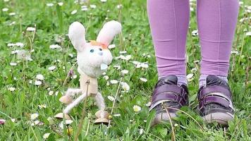 weiße Kaninchenmarionette, die auf grünem Gras tanzt
