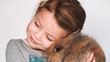 girl plays and cuddles with rabbit video
