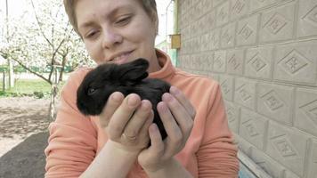 menina segura e acaricia o coelhinho preto