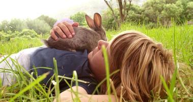 ragazzo gode del suo coniglietto sdraiato sull'erba all'esterno