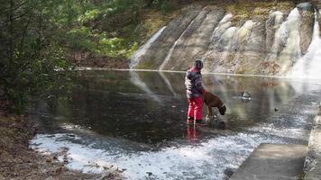 niño con perro en estanque congelado