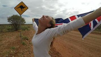junge Frau, die australische Flagge in der Luft nahe Känguruzeichen hält
