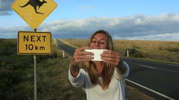 Young woman traveling takes selfie with kangaroo crossing sign video