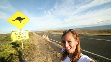 Young woman takes selfie portrait with warning road sign-Australia video