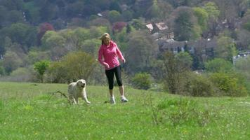 mulher madura com cachorro correndo no campo, filmado em r3d video