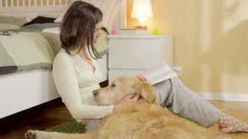 una ragazza che legge un libro con il suo cane a casa