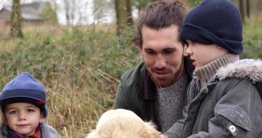Familia en invierno caminar en el campo con perro rodado en r3d video