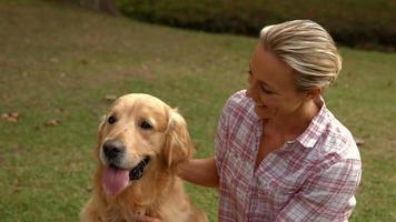Feliz mujer rubia con su perro en el parque