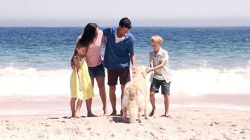 süße Familie, die mit dem Hund Ball spielt