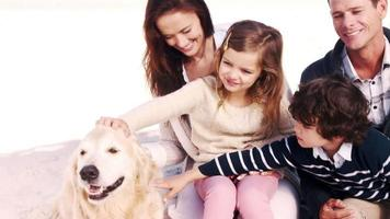 süße Familie, die einen Hund kuschelt video