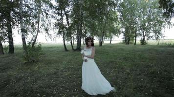 Braut hält ein Kaninchen in ihren Armen im Wald
