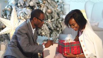 couple africain passe un bon moment près de l'arbre du nouvel an. l'homme présente un cadeau à la femme. cadeau surprise. incroyable lapin mignon en boîte.
