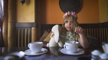 une petite fille prend le thé avec son lapin en peluche dans un café confortable video