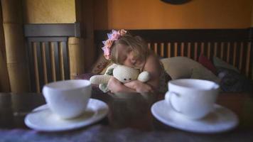 une petite jolie fille est assise sur le canapé dans un café et étreint son lapin en peluche