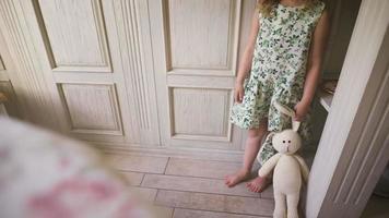 linda niña de pie en una habitación blanca sosteniendo un conejo de peluche video