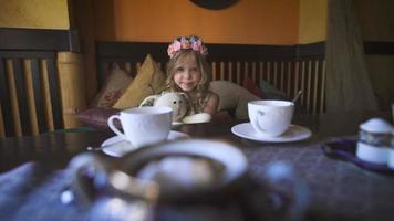 une petite fille heureuse est assise sur le canapé dans un café et étreint son lapin en peluche