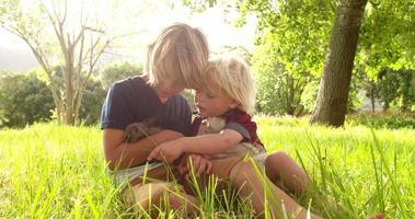 hermanos sosteniendo y alimentando a un lindo conejito en el parque