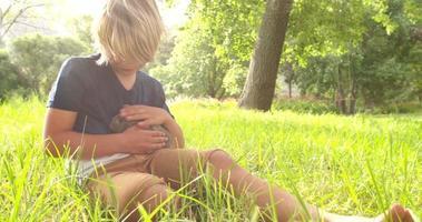 criança feliz cuidando de um coelho lá fora video