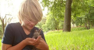 Happy child taking care of a bunny outside video