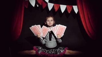 klein meisje toont focus met een grote speelkaarten