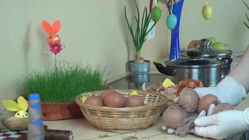 le mani con i guanti mettono le uova arrotolate nel calzino nell'acqua bollente con la vernice