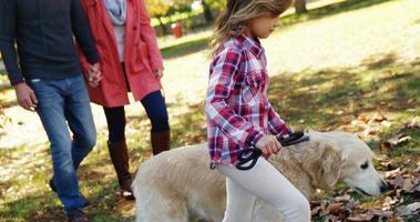 família passeando com cachorro ao ar livre