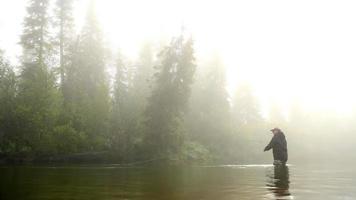 uomo annaspare in un pesce da un fiume avvolto dalla nebbia