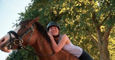 Mädchen, das sich liebevoll auf ihr Pferd stützt, während es in der Natur reitet