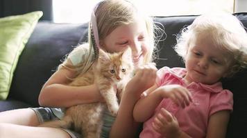 duas meninas sentadas em um sofá com um gatinho sorrindo