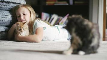 uma menina deitada no chão e acariciando um gatinho, com outro gatinho em primeiro plano video
