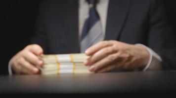 suborno: empresário toca um maço de dinheiro e o coloca sobre uma mesa (câmera escondida)
