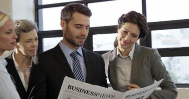 Geschäftsleute, die Zeitung betrachten