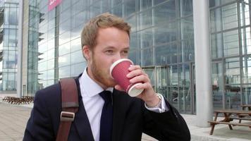 felice giovane imprenditore a piedi con il caffè in una strada cittadina video