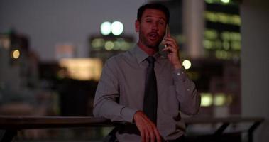 reifer Geschäftsmann, der auf dem Balkon am Telefon spricht