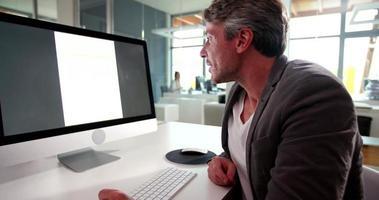 uomo d'affari maturo seduto alla scrivania guardando la presentazione del lavoro.