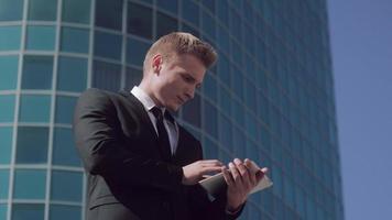 hombre de negocios concentrado está trabajando en su tableta al aire libre cuando recibe un agradable masaje