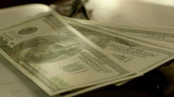 mettendo fascio di banconote in dollari sul libro