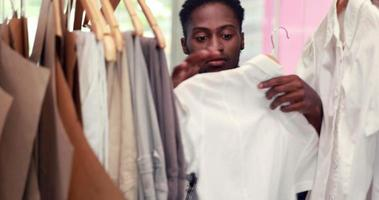 Male fashion designer looking at rack of clothes video