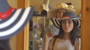 Dos mujeres jóvenes probándose sombreros en una tienda y mirarse en un espejo